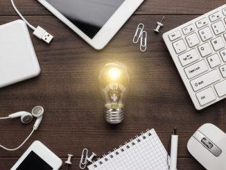 Glühbirne leuchtet neben PC-Tastatur und Smartphone