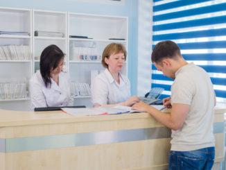 Mitarbeiterinnen mit Patient in Arztpraxis