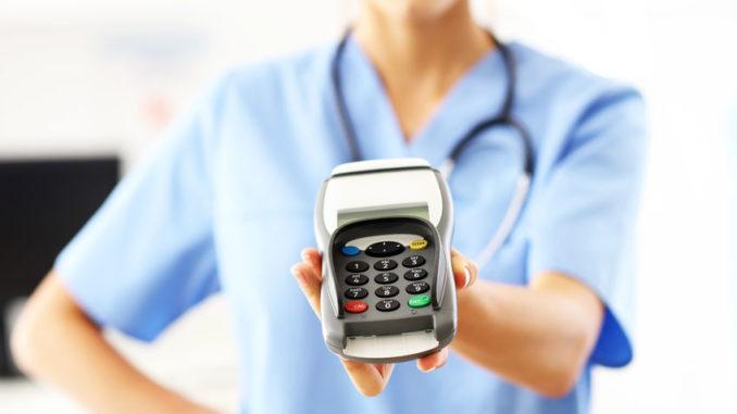 Ärztin hält Kartenterminal in Arztpraxis