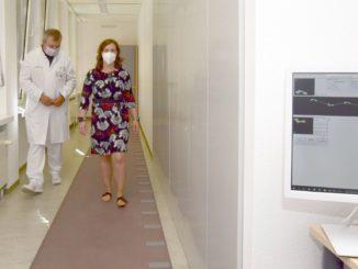 Professor Tjalf Ziemssen begleitet eine Patientin bei der Ganganalyse