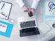 Mediziner nutzt am Schreibtisch mobile Computer