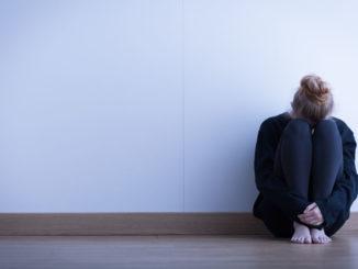 Frau sitzt auf Fußboden