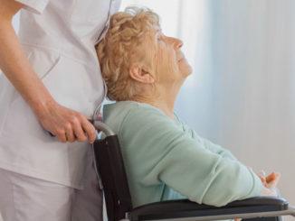 Seniorin wird im Rollstuhl geschoben