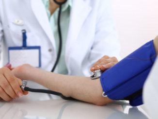 Mediziner kontrolliert Blutdruck
