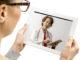 Frau spricht über Tablet-PC mit Ärztin