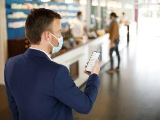 Patient mit E-Rezept auf dem Smartphone in Apotheke