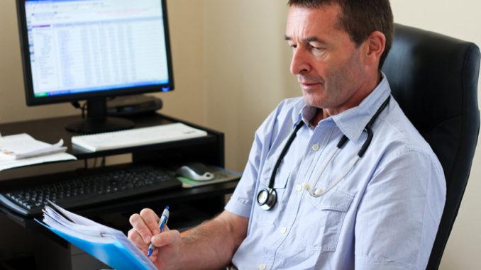 Mediziner bei Verwaltungsarbeit am PC