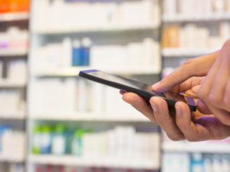 Person nutzt Smartphone in der Apotheke