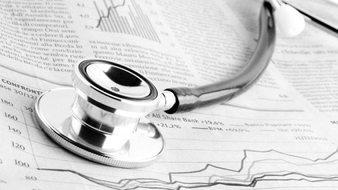 Stethoskop liegt auf Finanzzeitung