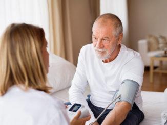 Pflegekraft misst beim Patienten den Blutdruck